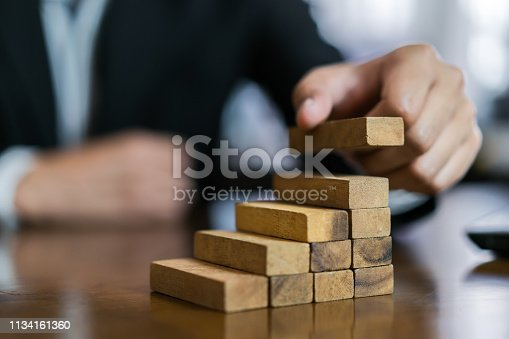 istock Businessman planing and strategy putting wooden blocks risk or success project hands control stack of danger tower challenge game building construction protect at office. 1134161360