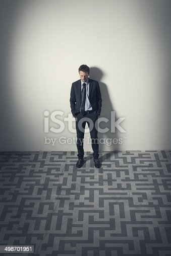 Pensive businessman looking at maze on the floor leaning to a wall.