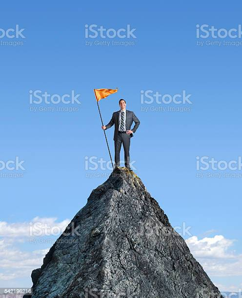 Photo of Businessman Planting A Flag On Top Of Mountain