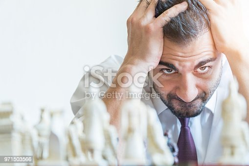Businessman playing chess and losing his game