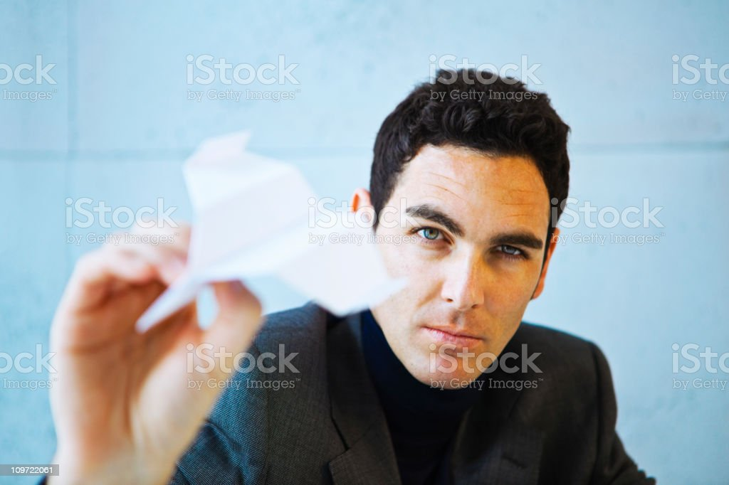Businessman playing with a paper plane while he brainstorms. royalty-free stock photo