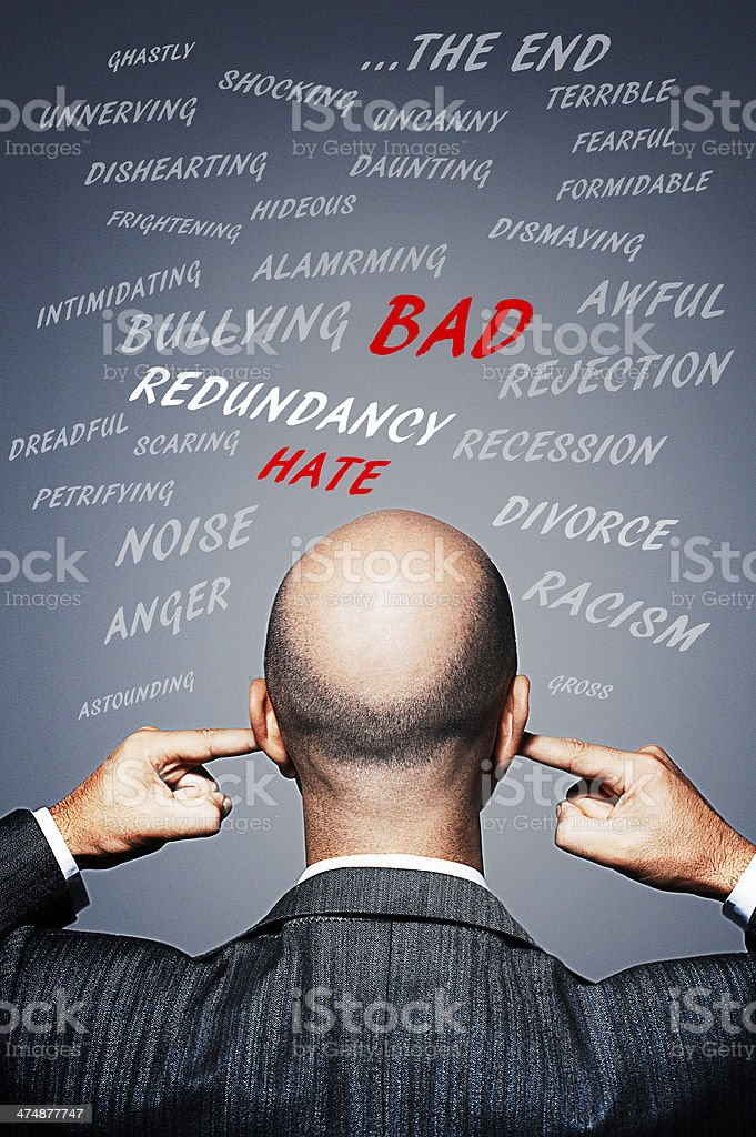 Businessman plugging his ears to avoid negative words and energy stock photo