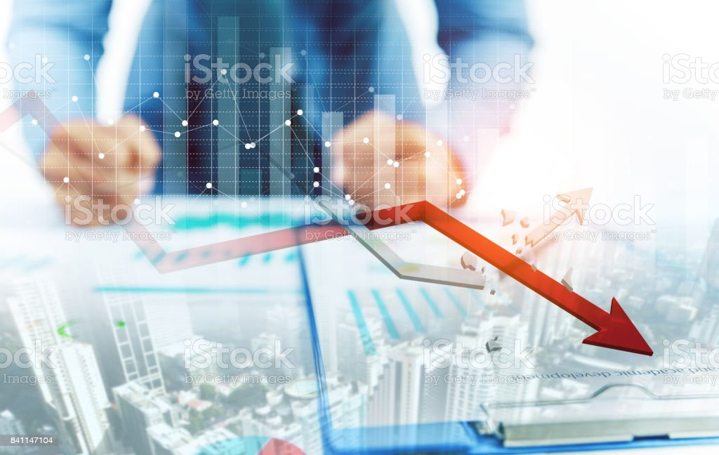 Businessman point at decreasing graph and increasing broken graph with city background stock photo