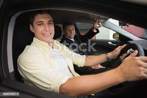 1138561232 istock photo Businessman pointing a car interior 468593514