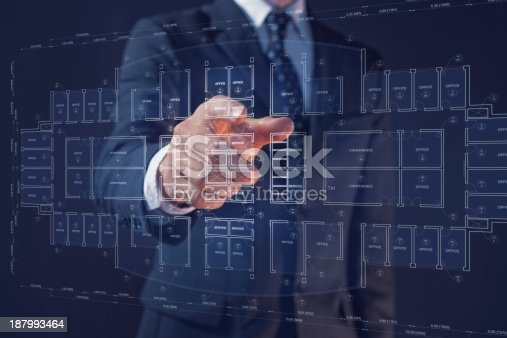 istock Businessman pointing a display with an office architecture interactive blueprint 187993464