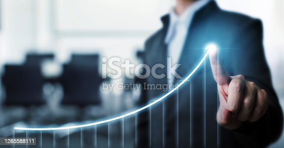 Businessman pointing arrow graph corporate future growth plan with blurred background office. Business development to success and growing growth concept.