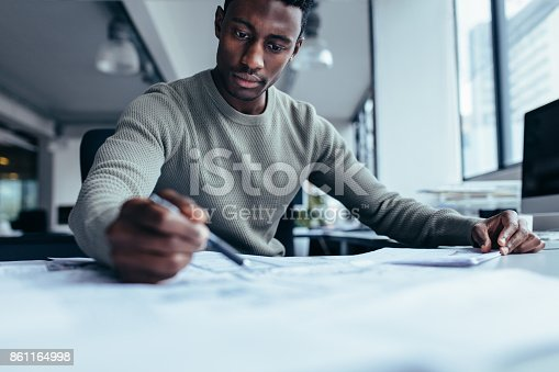 istock Businessman pointing at building plan in office 861164998