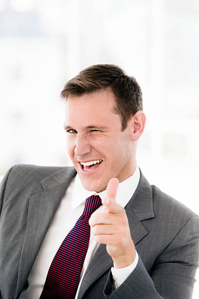 Businessman pointing at camera Portrait of a successful young businessman pointing at camera and winking cheesy grin stock pictures, royalty-free photos & images