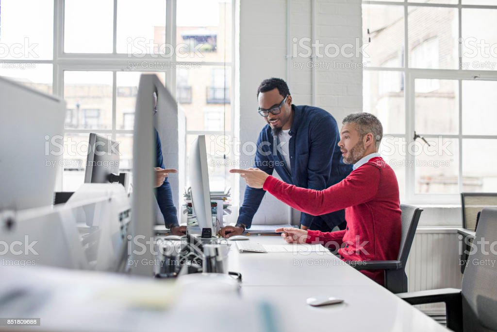 Businessman pointing at computer to colleague stock photo