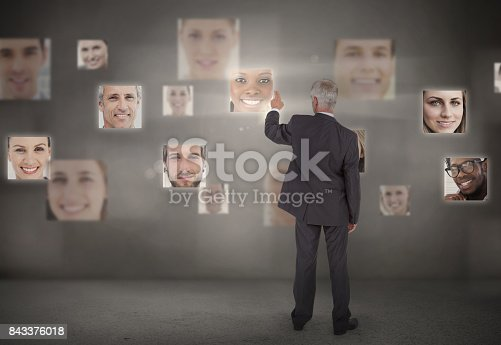 Businessman pointing at digital interface showing faces