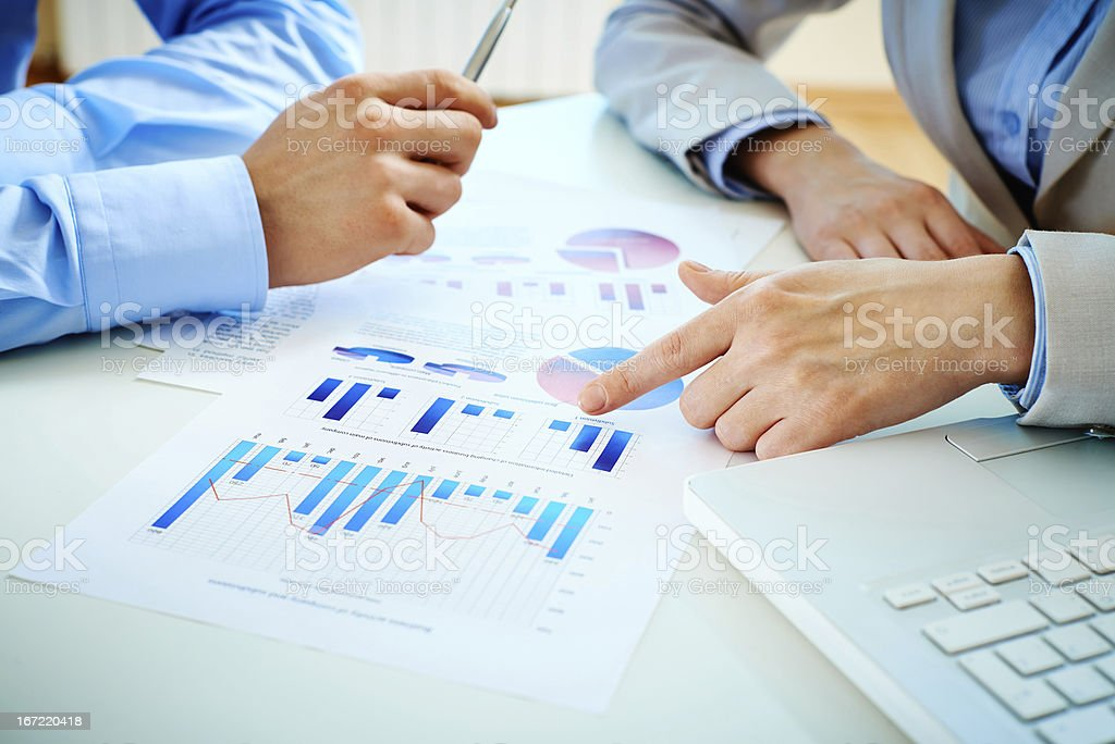 Businessman pointing at graphs on a page royalty-free stock photo