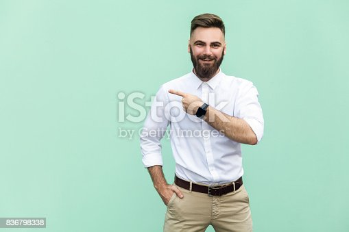 istock Businessman pointing copy space. Handsome young adult man with beard in white shirt looking at camera and pointing away while standing isolated on white background 836798338