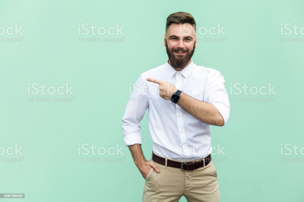 Businessman pointing copy space. Handsome young adult man with beard in white shirt looking at camera and pointing away while standing isolated on white background stock photo