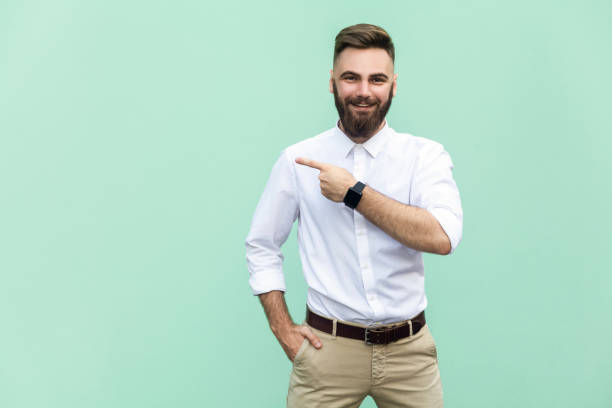 businessman pointing copy space. handsome young adult man with beard in white shirt looking at camera and pointing away while standing isolated on white background - isolated colour stock photos and pictures