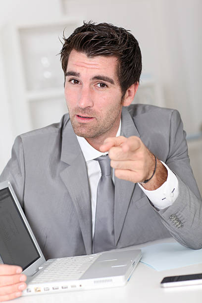 Businessman pointing finger to camera stock photo