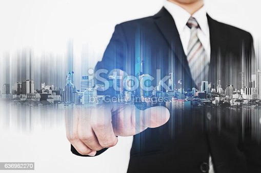 635942136istockphoto Businessman pointing finger to screen, with technology graphic modern buildings 636962270