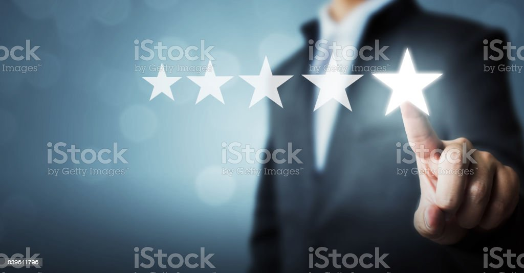 Businessman pointing five star symbol to increase rating of company stock photo