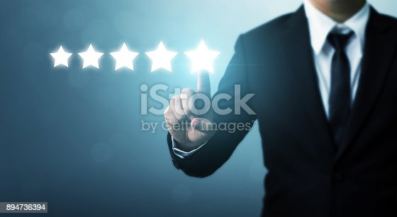 istock Businessman pointing five star symbol to increase rating of company 894736394