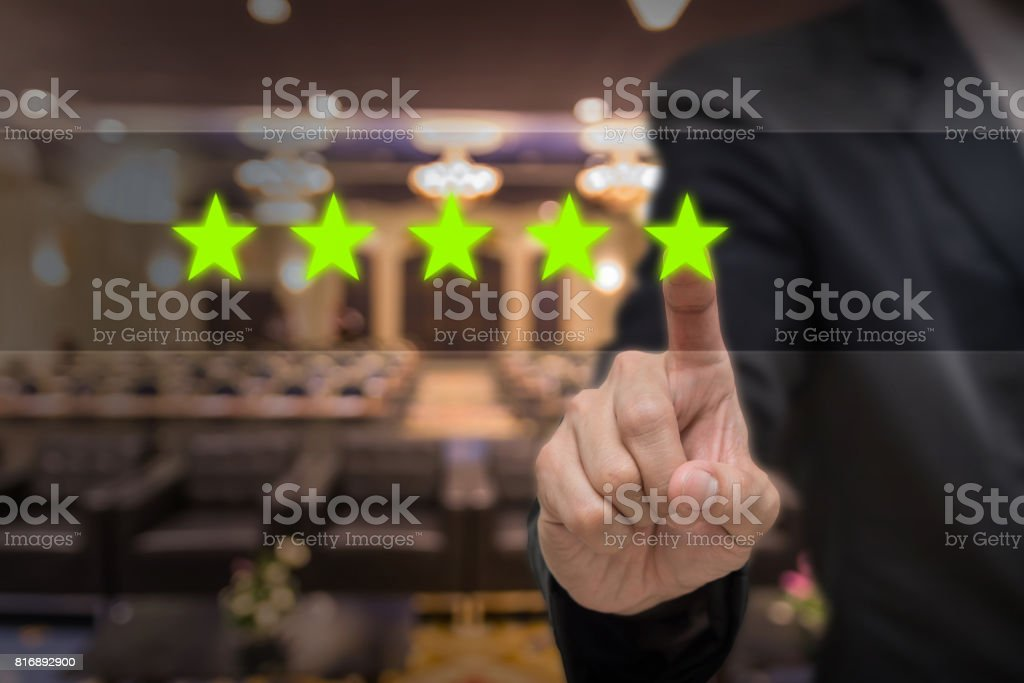 Businessman pointing five star symbol to increase rating of hotel over Abstract blurred photo of conference hall or seminar room with attendee background, business evaluation concept, Increase rating stock photo