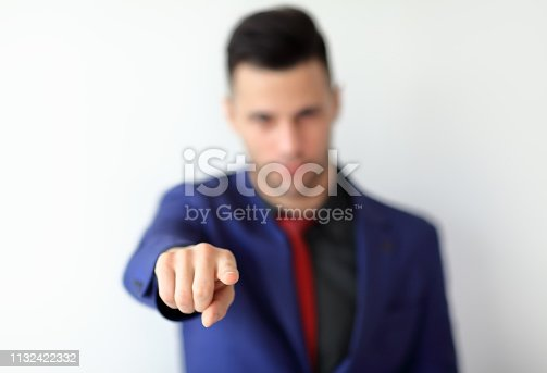 Businessman in suit pointing his finger at you