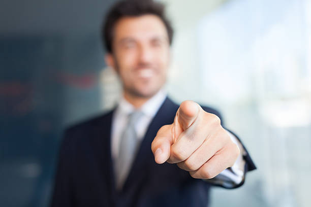 Businessman pointing his finger at you stock photo