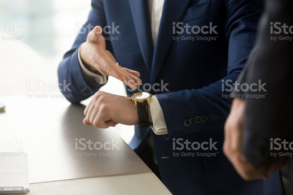 Businessman pointing on wristwatch, punctuality, time management concept, close up stock photo