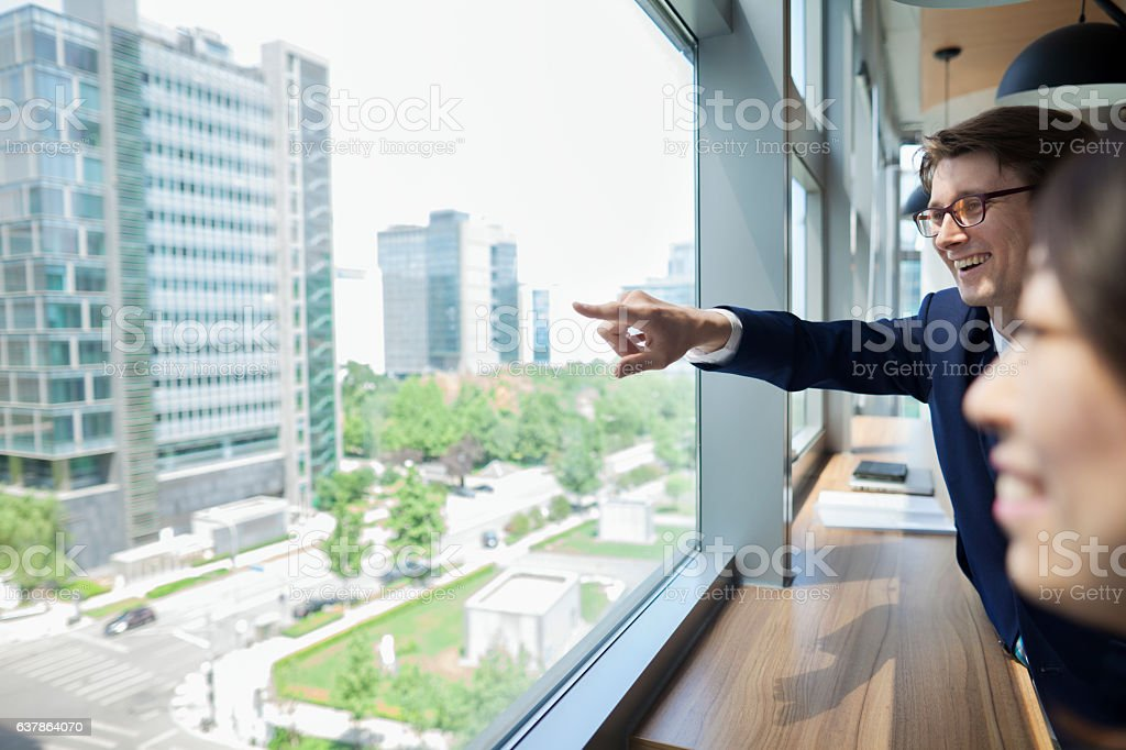Businessman pointing to scene through window