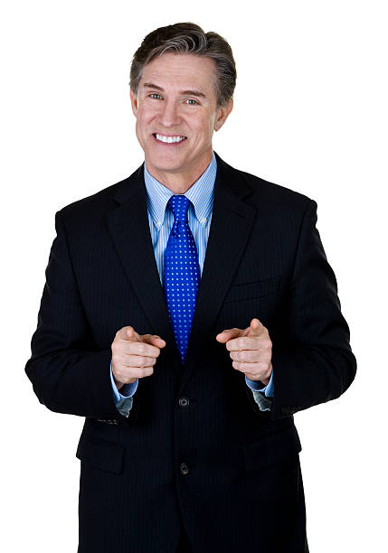 Businessman pointing to viewer Vertical composition of a mature businessman pointing to viewer  cheesy grin stock pictures, royalty-free photos & images