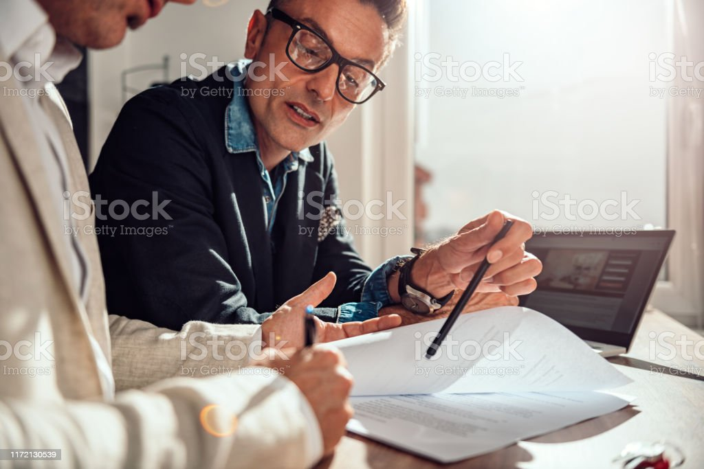 Businessman pointing where client have to sign the contract Businessman pointing place in contract where client have to sing Adult Stock Photo