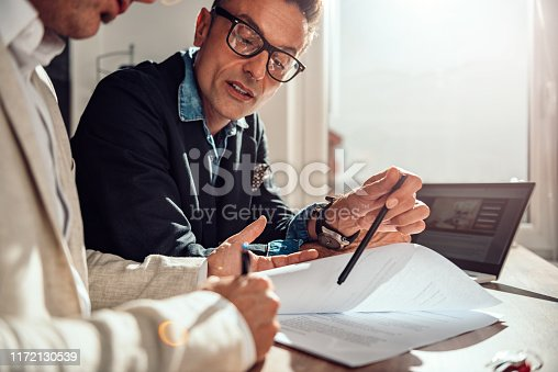 istock Businessman pointing where client have to sign the contract 1172130539
