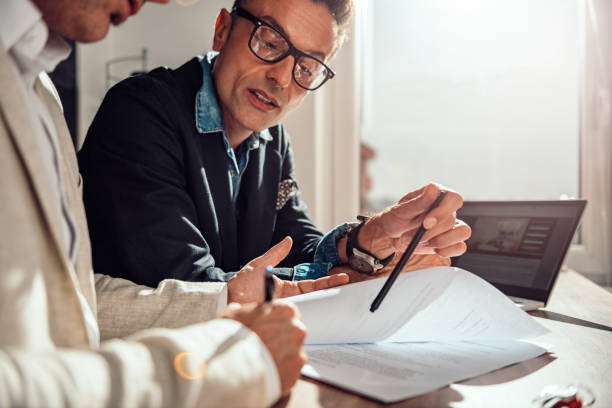 Geschäftsmann zeigt, wo der Kunde den Vertrag unterzeichnen muss – Foto