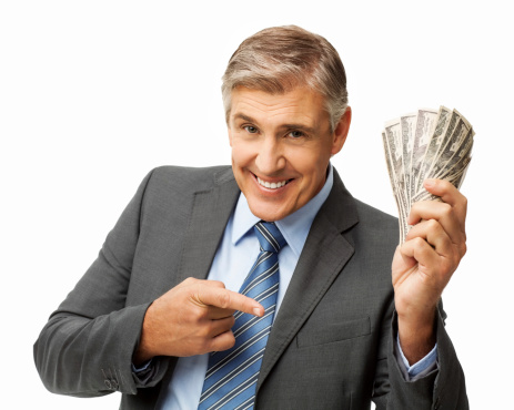 Portrait of happy businessman pointing while holding fanned money over white background. Horizontal shot.