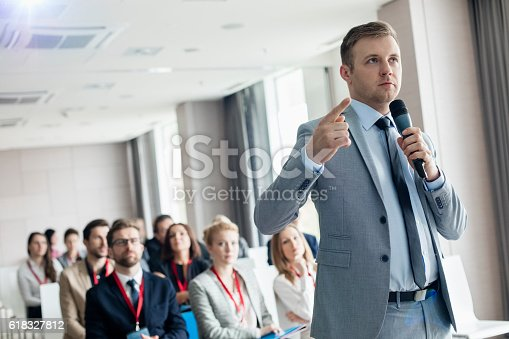 istock Businessman pointing while speaking through microphone 618327812