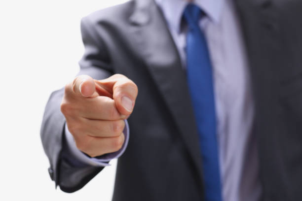 Businessman points a finger at someone who stock photo
