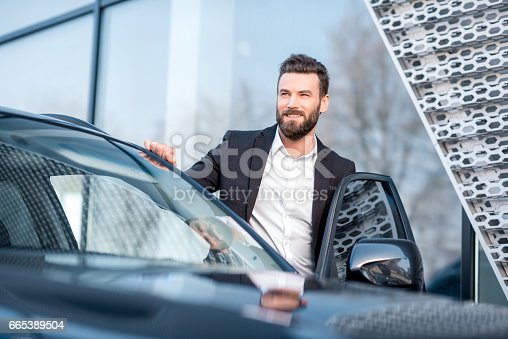 istock Businessman portrait near the car 665389504