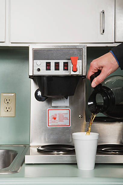 Businessman pouring a coffee Businessman pouring a coffee coffee pot stock pictures, royalty-free photos & images