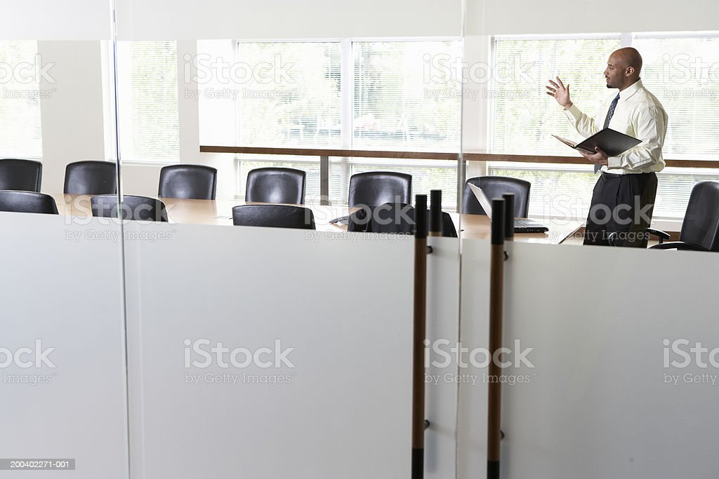 Businessman practicing presentation in boardroom, side view stock photo