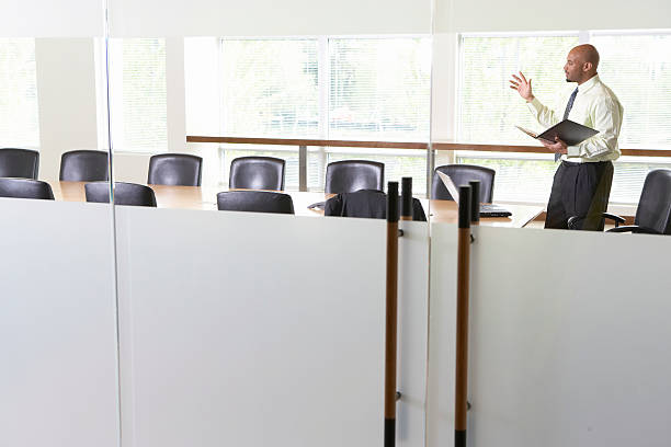 businessman practicing presentation in boardroom, side view - practising stock photos and pictures