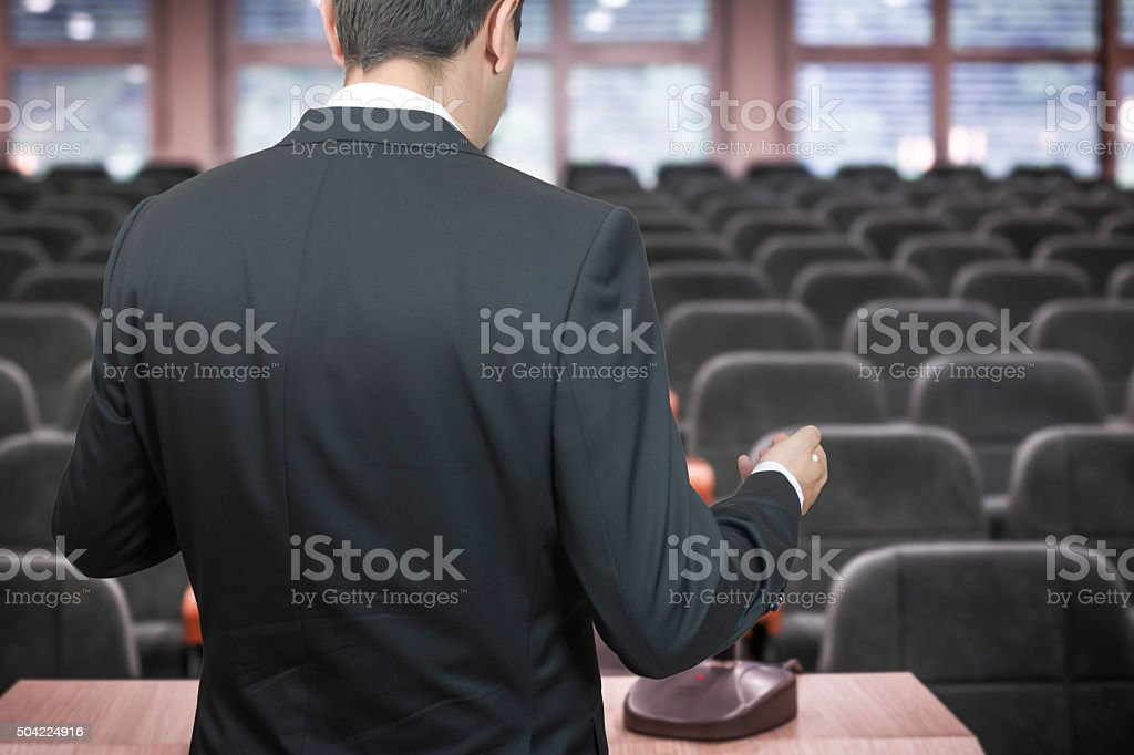 Businessman practising his speech in emtry conference room stock photo