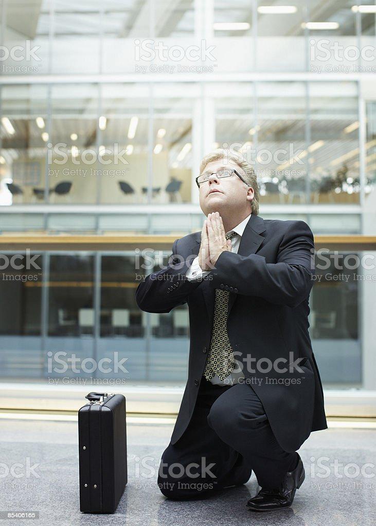 Businessman praying in building lobby stock photo