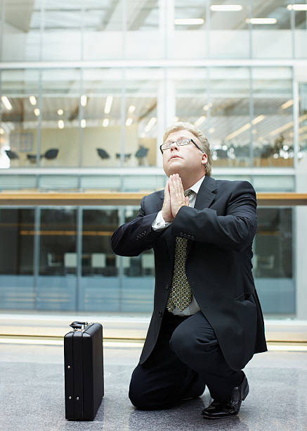 Businessman praying in building lobby stock photo