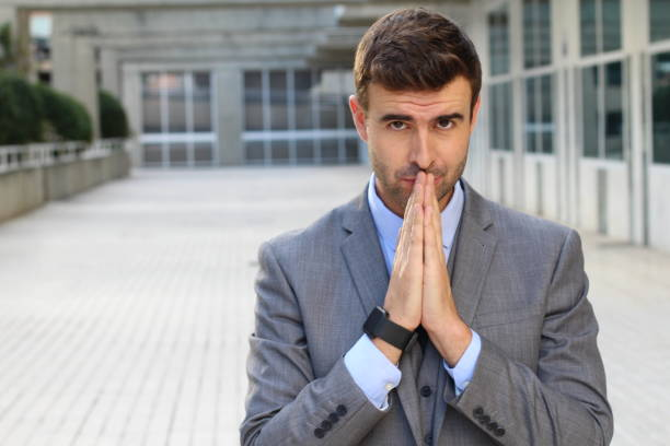 Businessman praying in the office stock photo