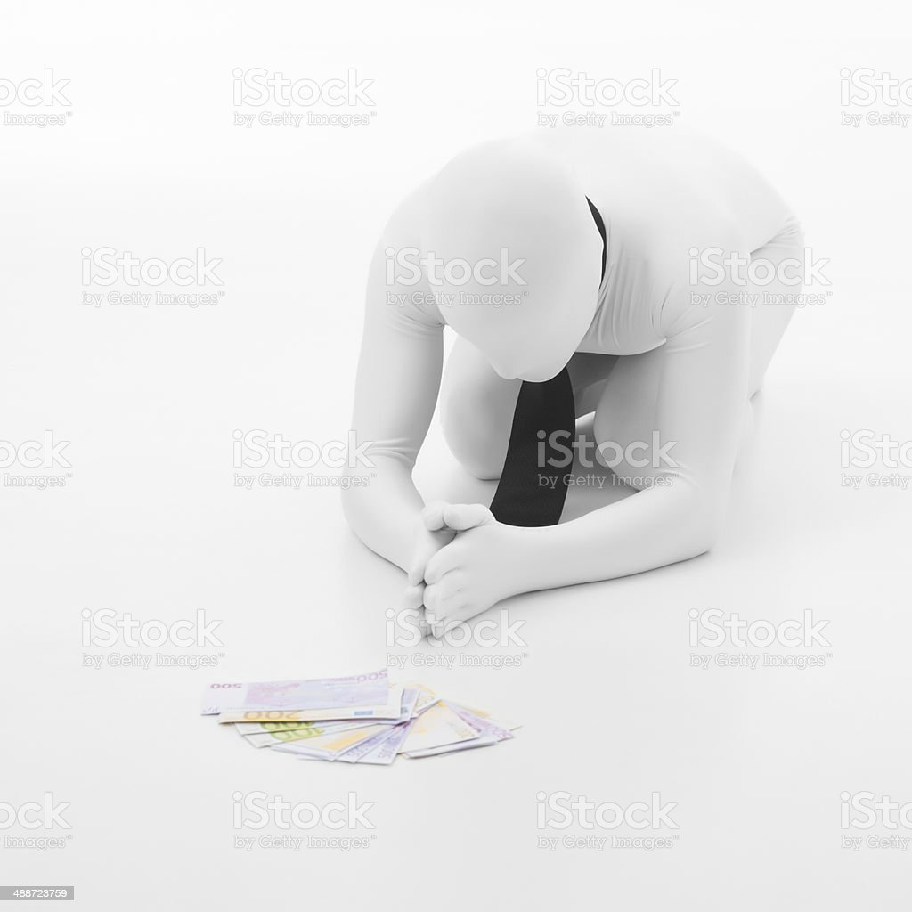 businessman prays to money royalty-free stock photo