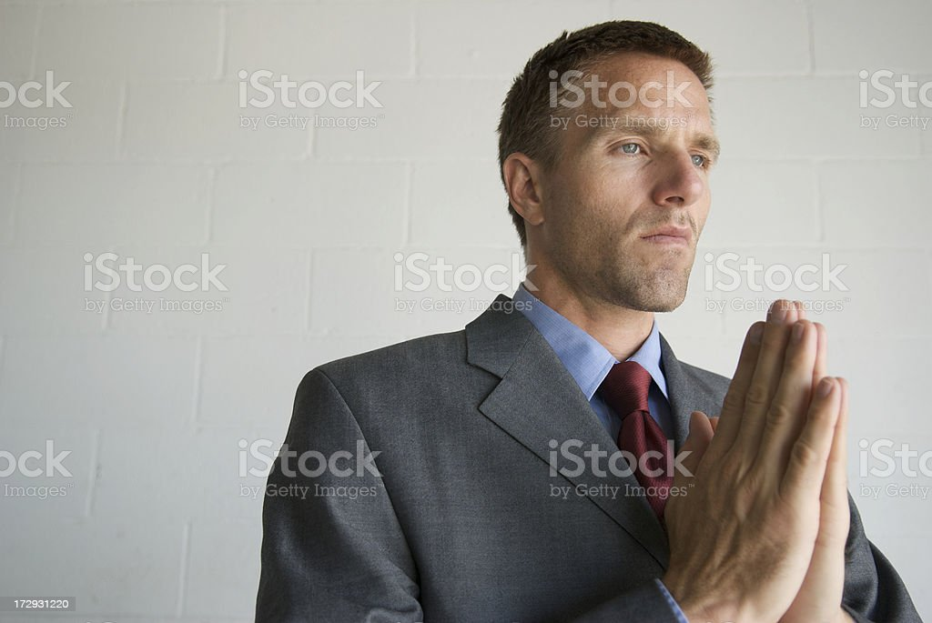 Businessman Prays with Hands Clasped stock photo