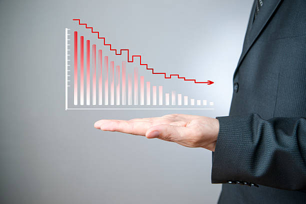 Businessman presenting a sustainable decrease development Business concept. Businessman presenting a sustainable decrease development on a bar chart on gray background. negative image technique stock pictures, royalty-free photos & images