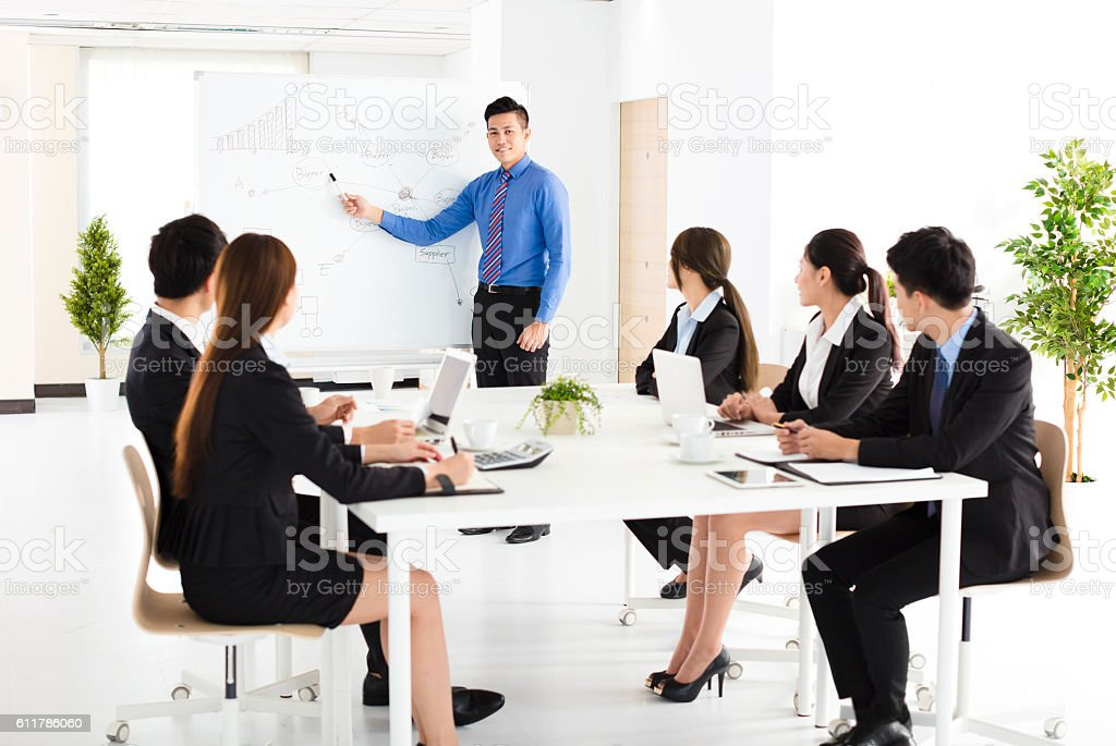 Businessman presenting new project to partners in office stock photo