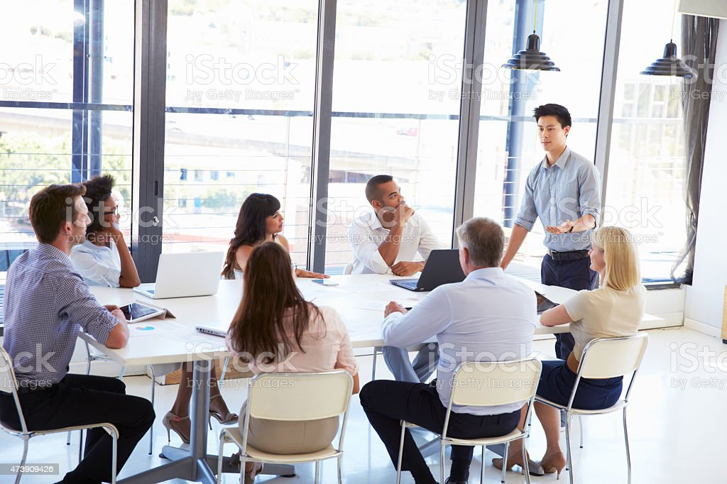 Businessman presenting to colleagues at a meeting stock photo