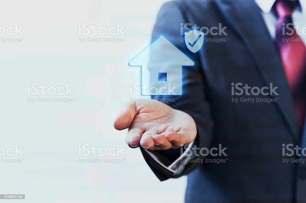 Businessman presenting virtual house with protection on his palm stock photo