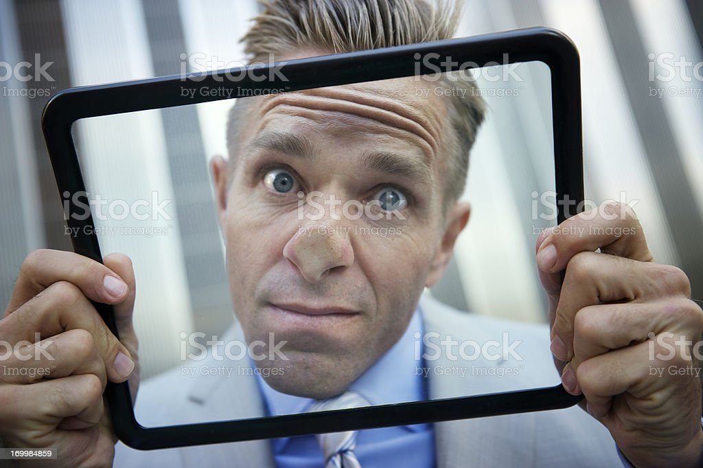 Businessman Presses His Nose Against Tablet Computer stock photo