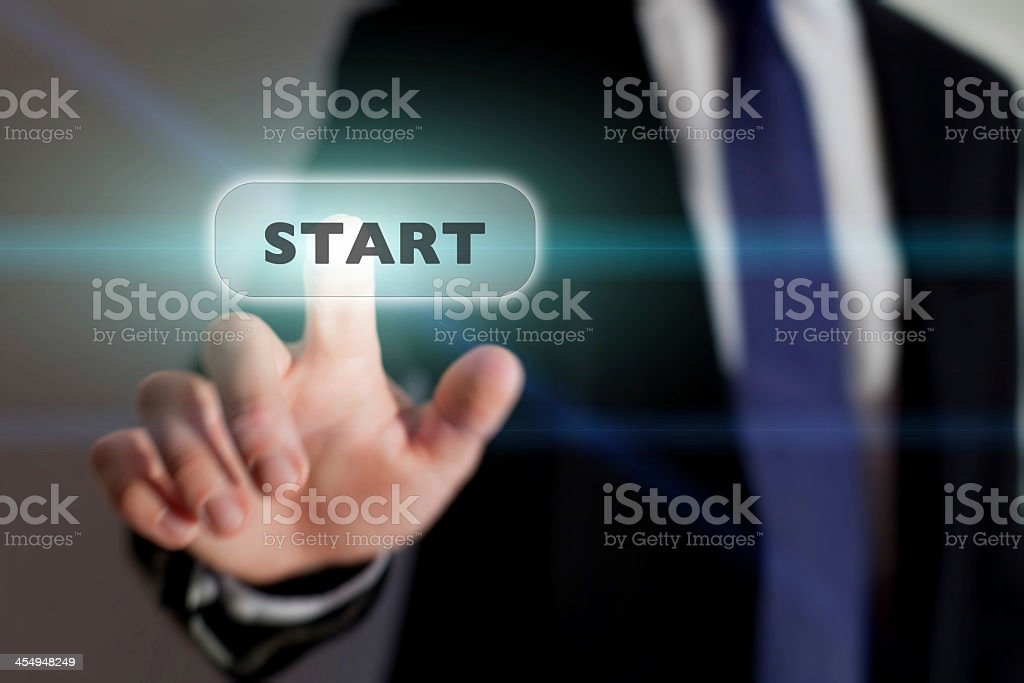 Businessman pressing a start icon on a transparent screen stock photo